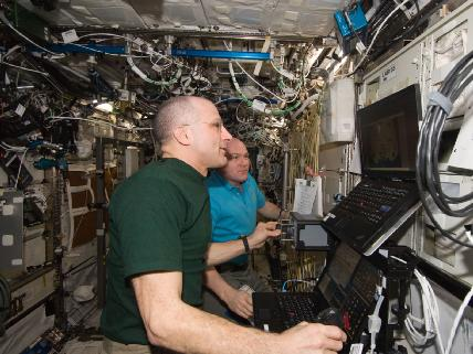 In the International Space Station's Destiny laboratory, NASA astronaut Don Pettit (foreground) and European Space Agency astronaut Andre Kuipers, both Expedition 30 flight engineers, conduct the first of three sessions on the ROBoT simulator in preparation for the arrival of the SpaceX Dragon. Photo credit NASA.