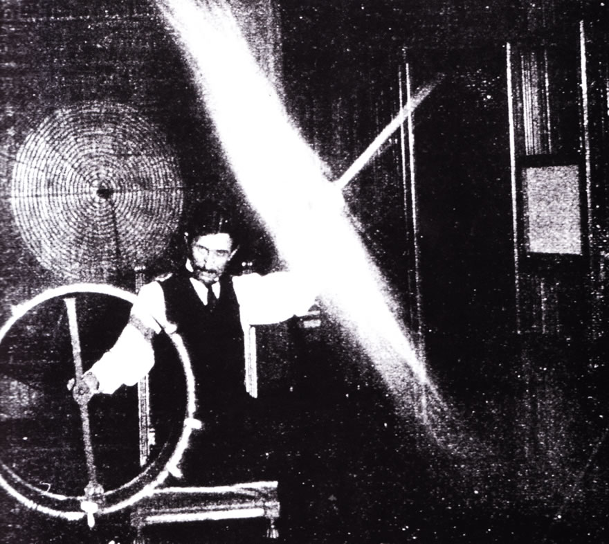 Tesla at his Houston street laboratory in 1898, sending 500,000 volts through his body to light a wireless fluorescent light. Image source Wiki commons.